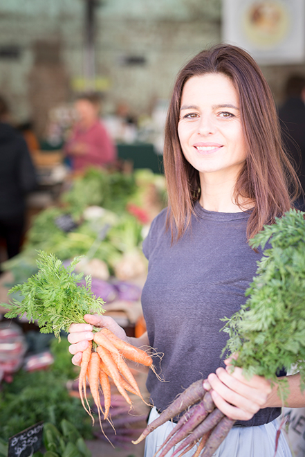 Woman holding two bunches of carrots at a market